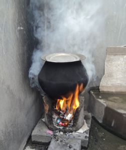 Burning biofuel cakes for cooking in Tamil Nadu, India